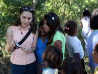 Jean Friedman-Rudovsky (left) showing photographs on her camera to a group of kids living near sugar cane fields outside of Santa Cruz, Bolivia, in 2011, while reporting a story on the unionization of child workers.